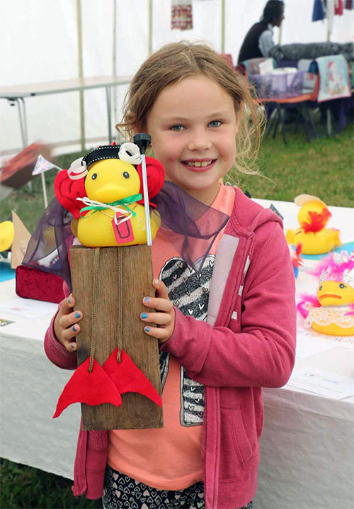 A splendid competitor in our popular Best-Dressed Duck contest with its proud creator.